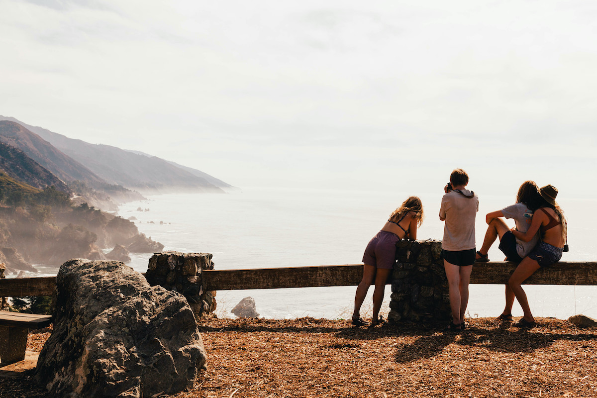 Group of young people at scenic overlook of the coast gazing out into the fog-shrouded hills and ocean in the distance