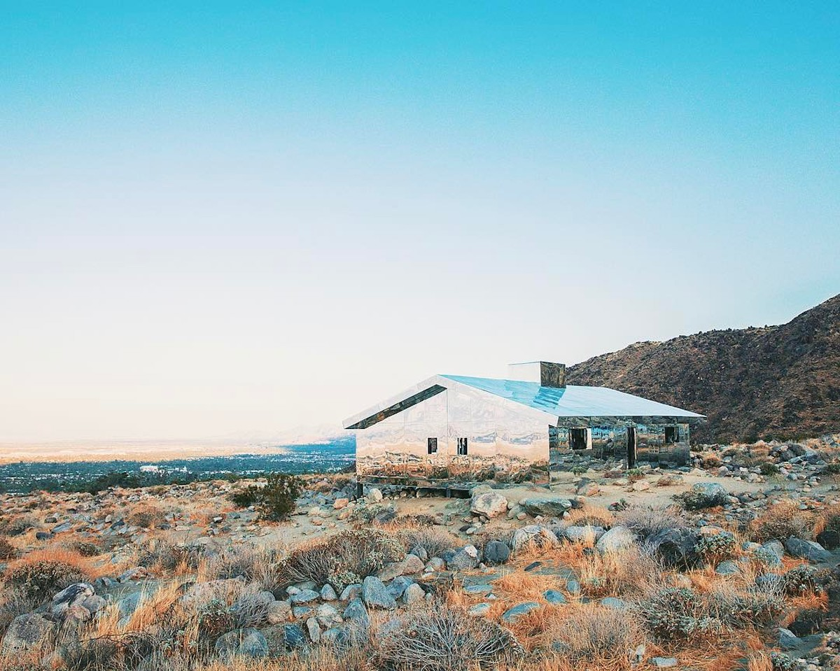 Mirrored house reflecting the views of a desert prairie with mountains in the background