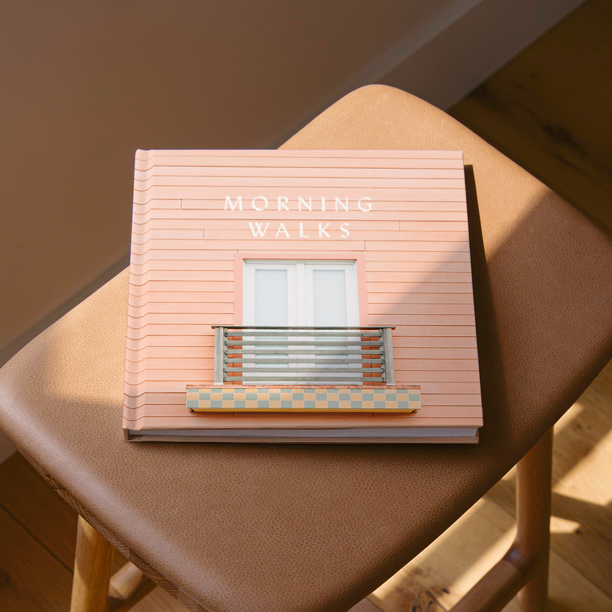 Artifact Uprising Photo-Wrapped Hardcover Book titled Morning Walks featuring photo of picturesque patio on the cover