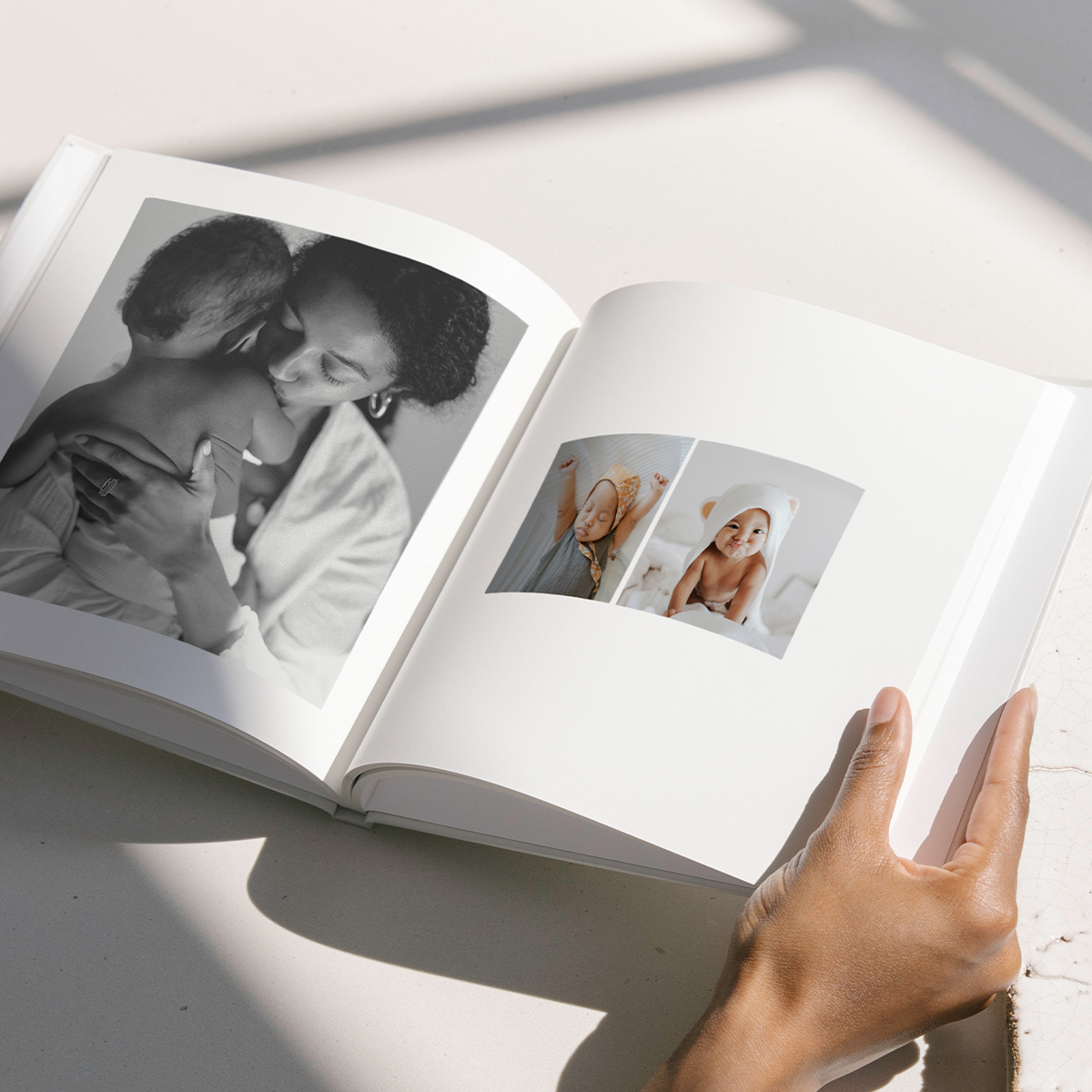 Interior pages of Artifact Uprising Photo-Wrapped Hardcover showing baby photos arranged in a different layout on either page