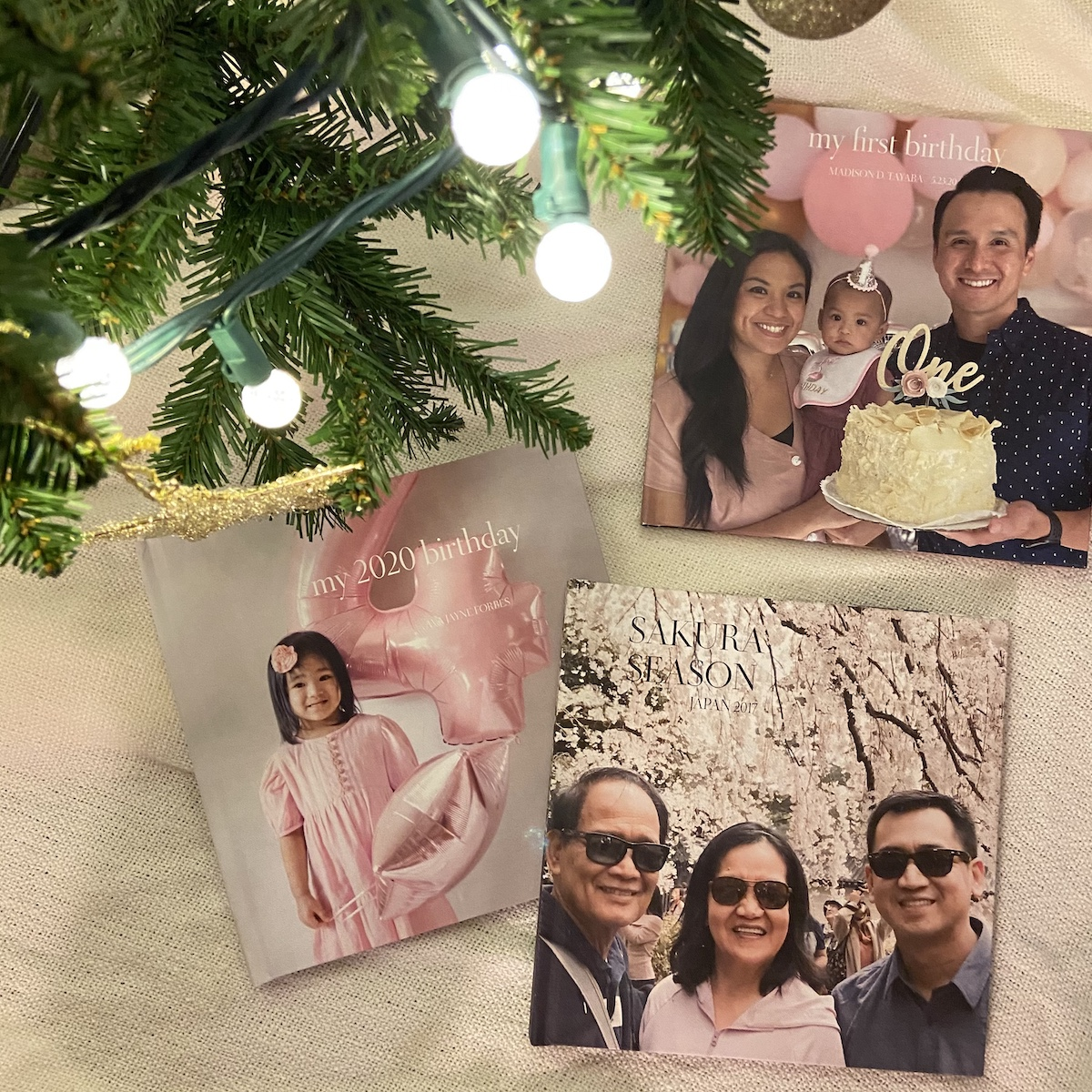 Multiple Artifact Uprising Photo-Wrapped Hardcover books commemorating birthdays resting under a Christmas tree with bulb lights