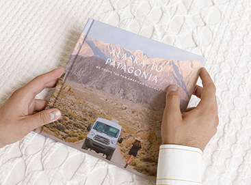 Hands holding Artifact Uprising Photo-Wrapped Hardcover Book titled Alaska to Patagonia featuring photo of camper van in front of mountainous landscape