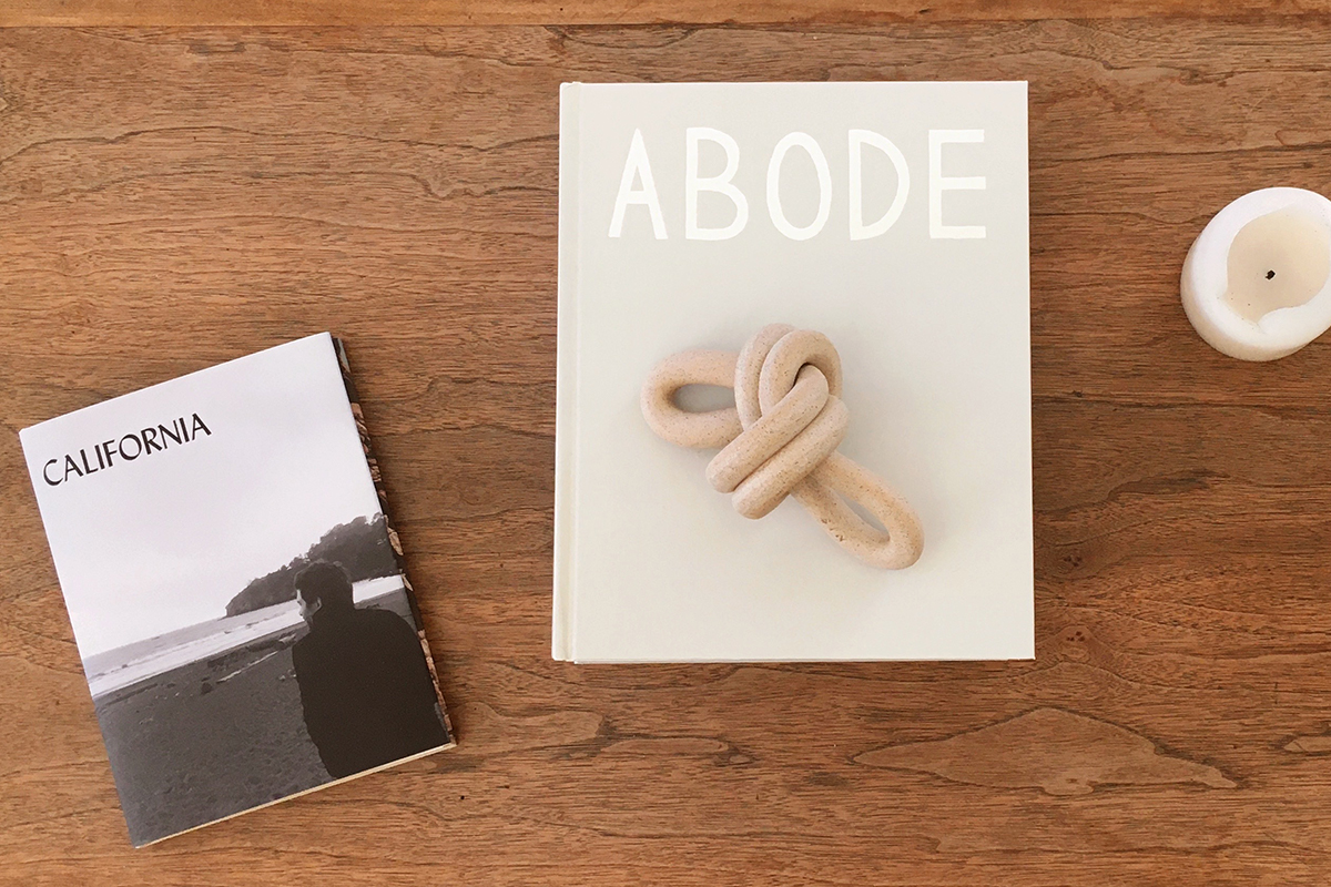 Custom coffee table book titled Abode resting on coffee table