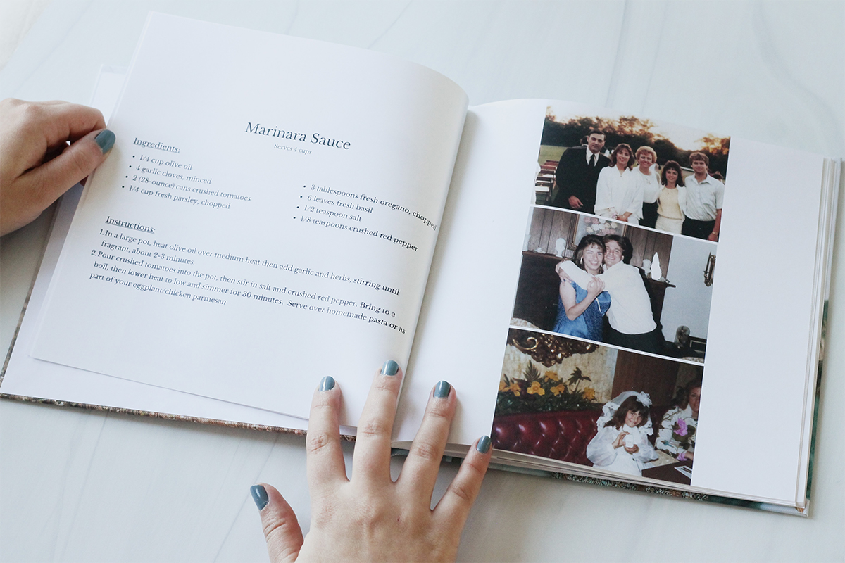 Custom family cookbook opened to recipe for Marinara Sauce on left page and family photos on right page