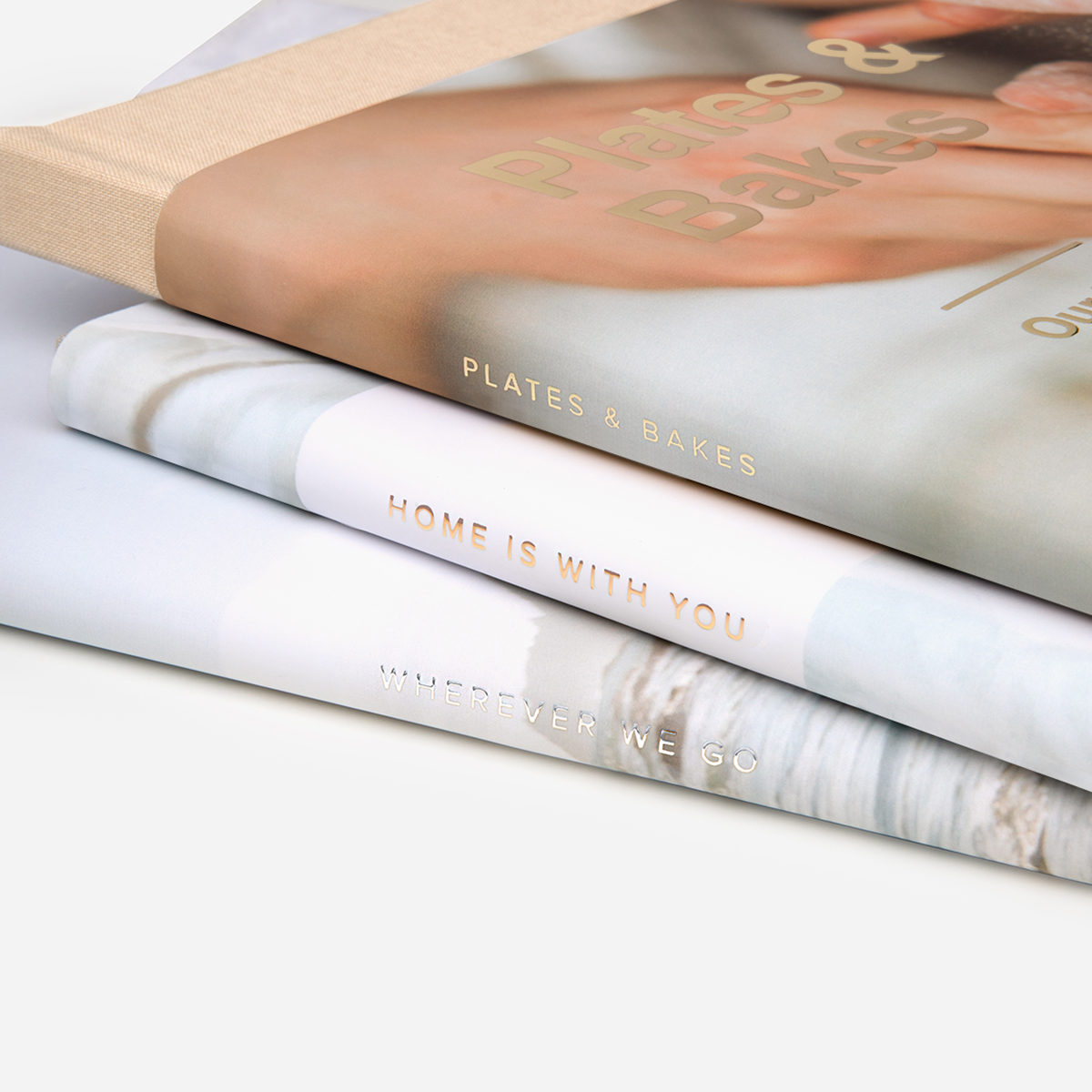 Digital foil lettering on the spines of the dust jackets of three stacked Artifact Uprising Hardcover Photo Books