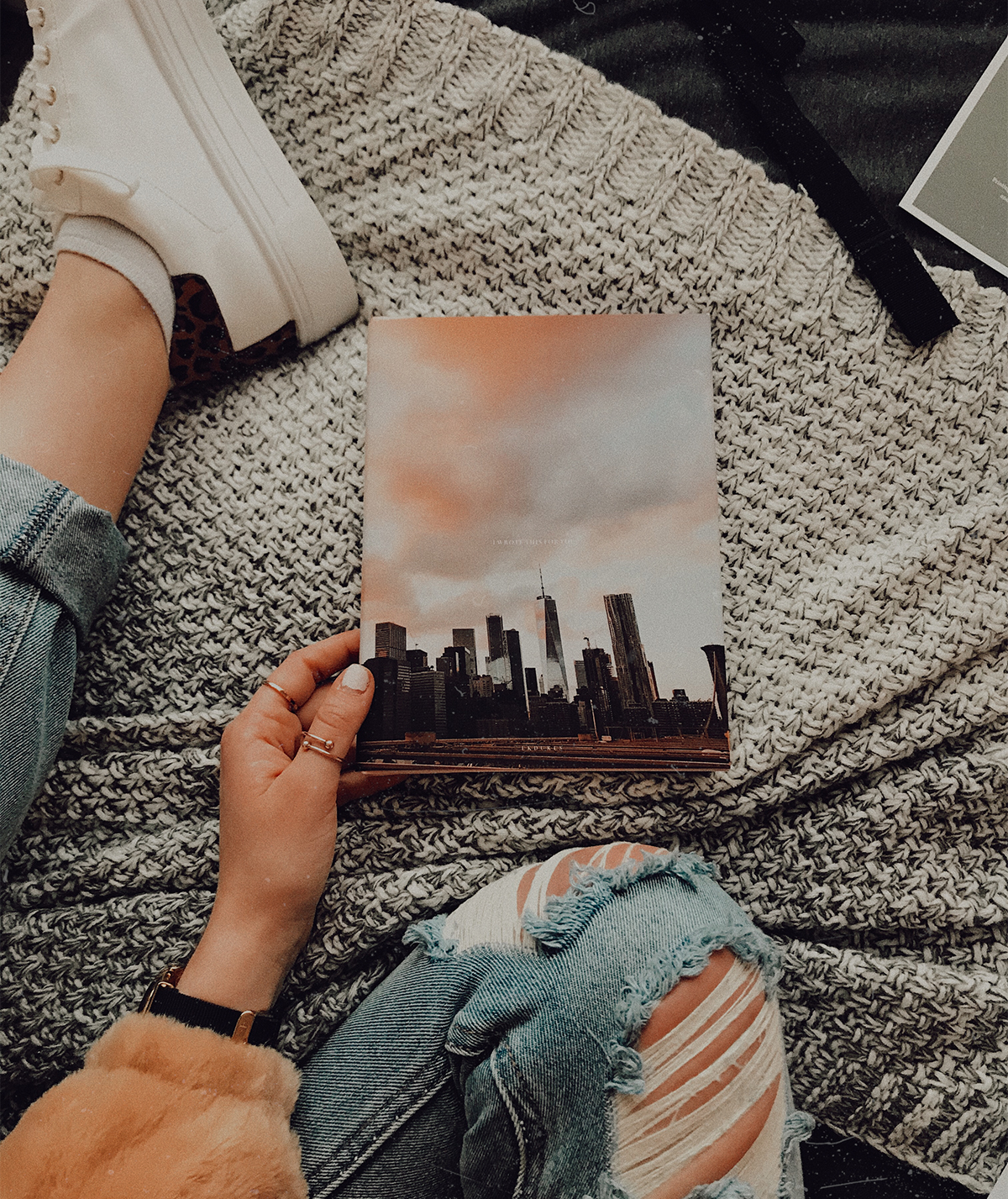Woman sitting on bed with Artifact Uprising Hardcover Photo Book in her lap featuring photo of city skyline at sunset on the cover