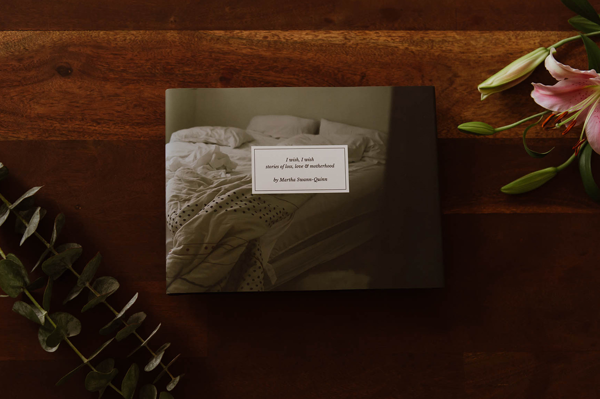 Artifact Uprising Hardcover Photo Book titled I Wish, I Wish on wooden surface between lillies and eucalyptus