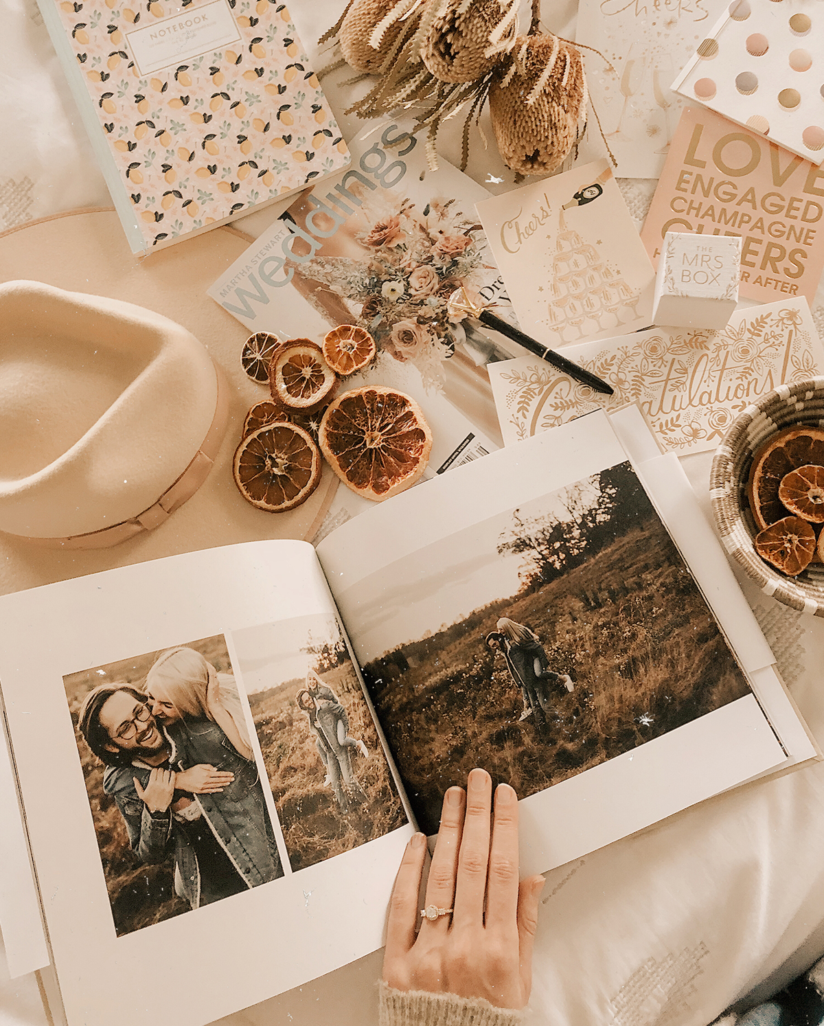 Artifact Uprising Hardcover Photo Book opened to engagement photos on table covered with wedding stationery and planning materials