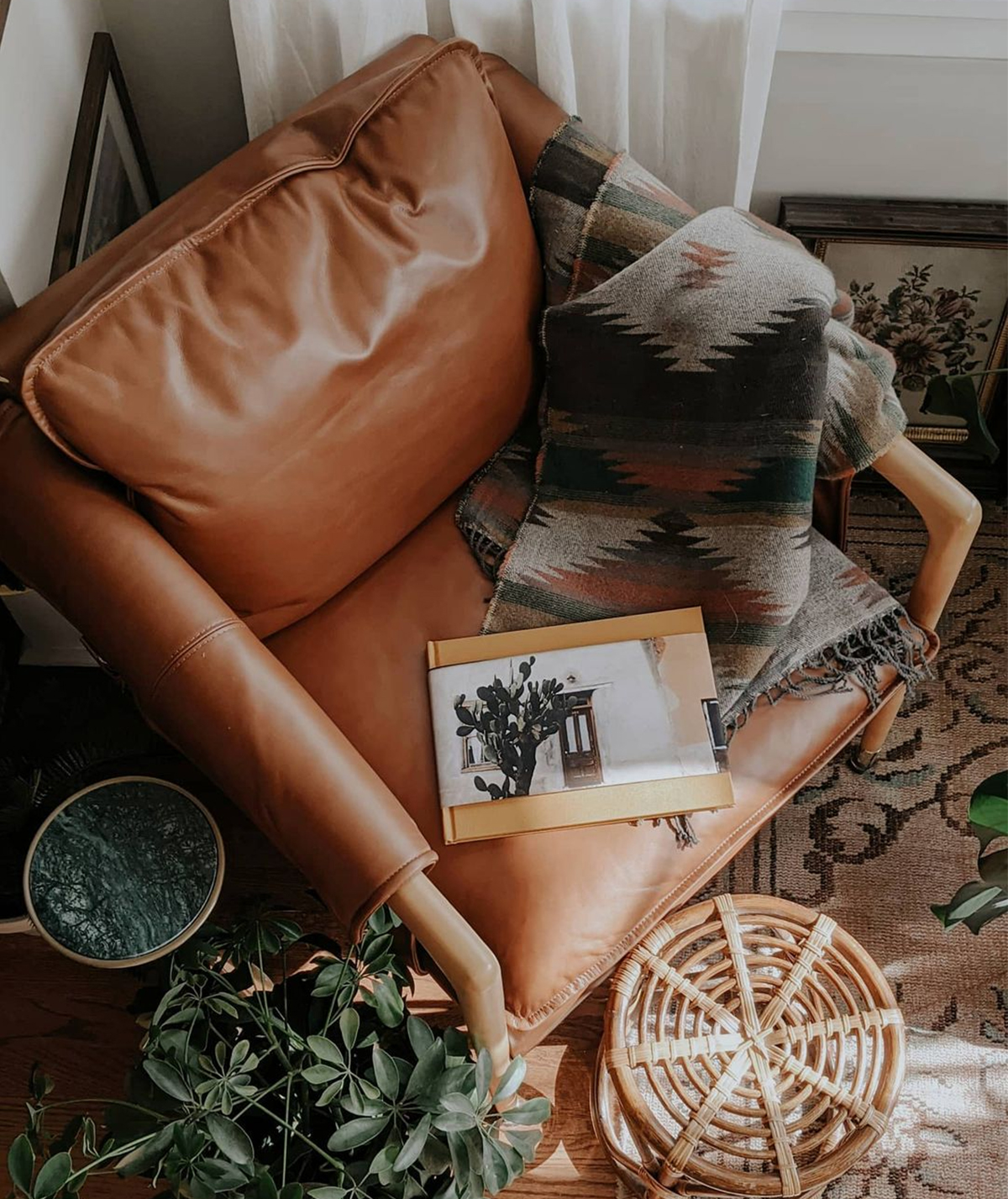 Artifact Uprising Photo Book printed as a travel album laying on leather armchair next to patterned throw blanket