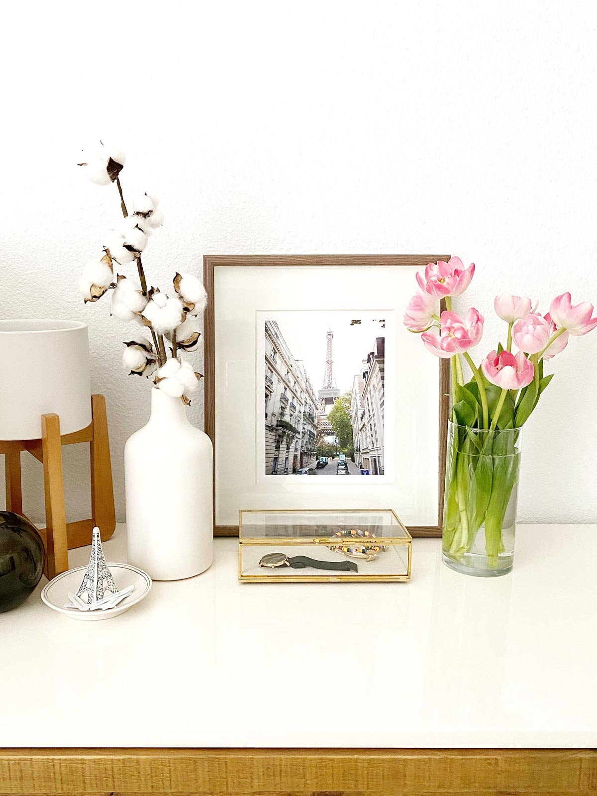 Image 1: Artifact Uprising Metal Tabletop Frame on a dresser next to vibrant flowers.