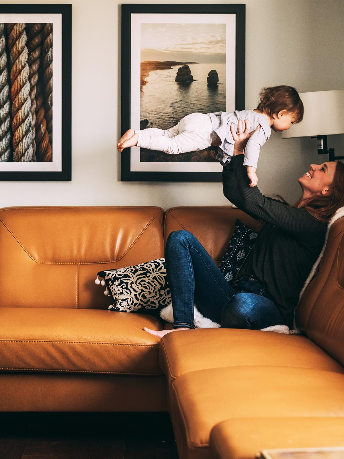 Mom holding toddler up in front of Gallery wall hanging above caramel leather couch