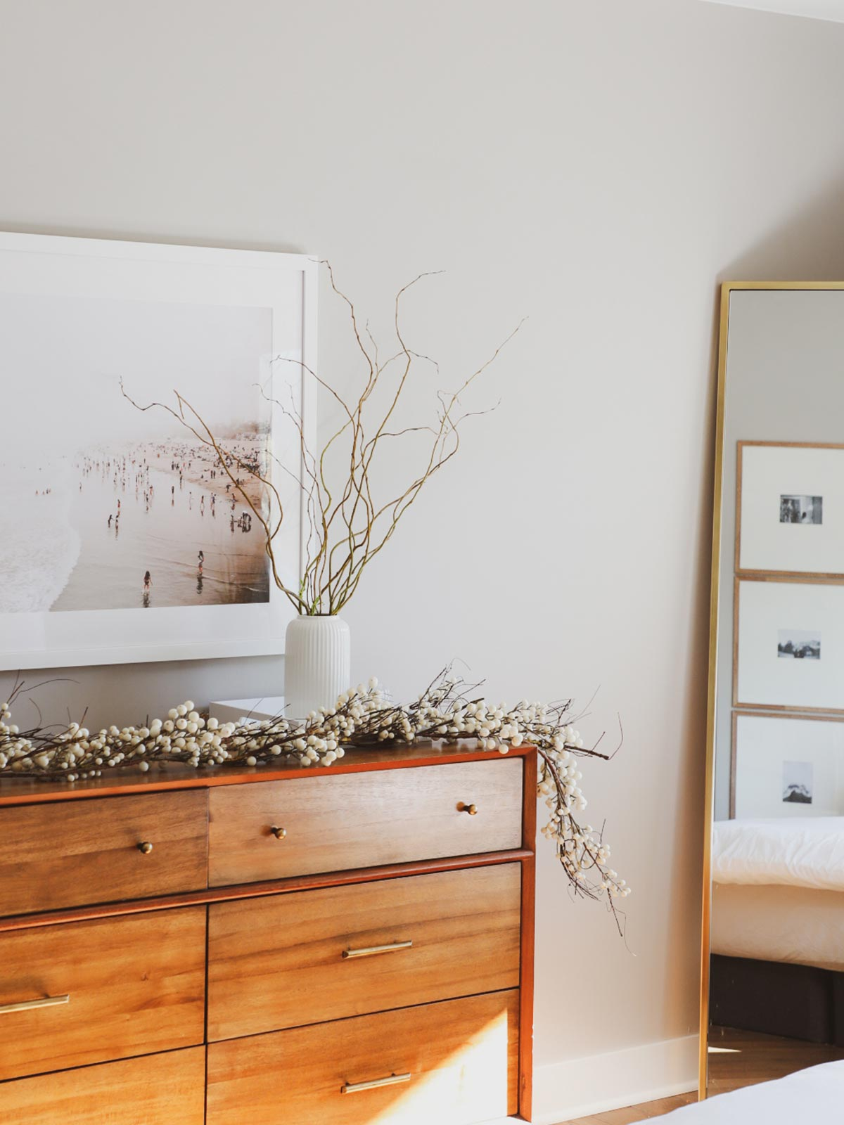 Gallery Frame featuring photo of the beach on bedroom wall above dresser with dried branches in vase.