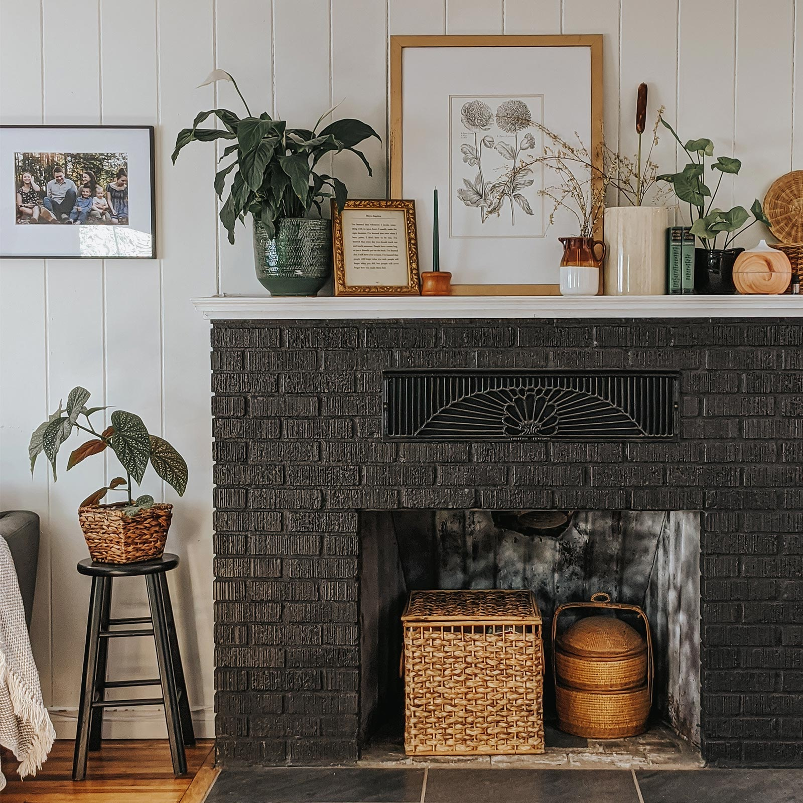 Mantel of black brick fireplace filled with frames, plants, and other ornamentals