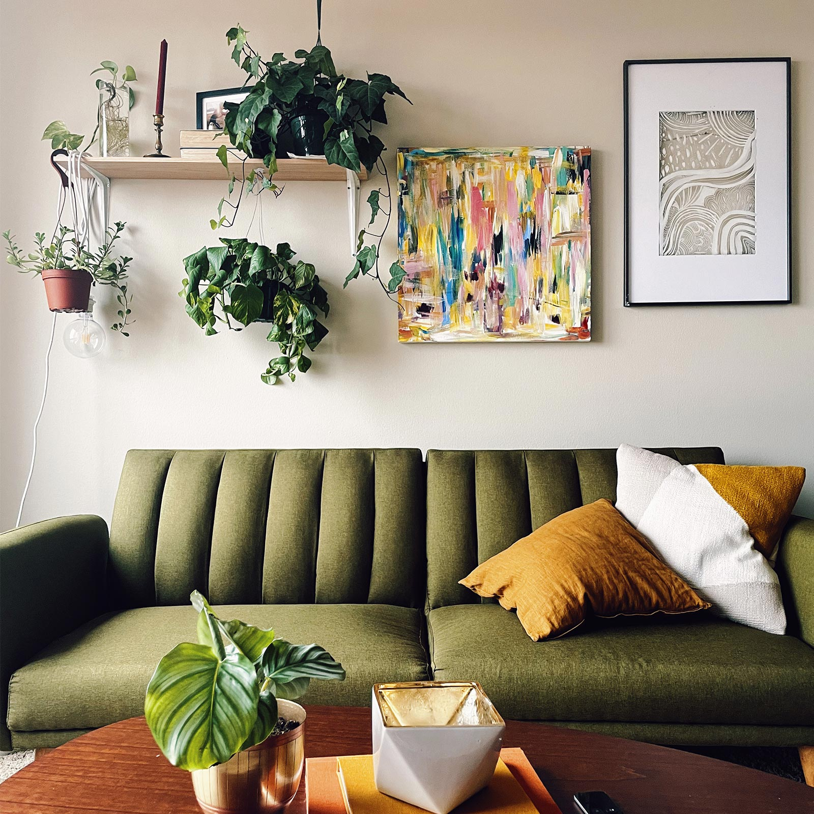 Stack of Artifact Uprising photo books on coffee table in front of mid-century modern olive green velvet couch