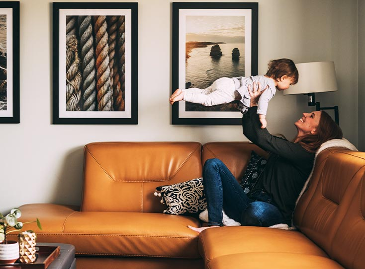 Woman on orange leather couch holding up young child in front of a three-frame gallery wall