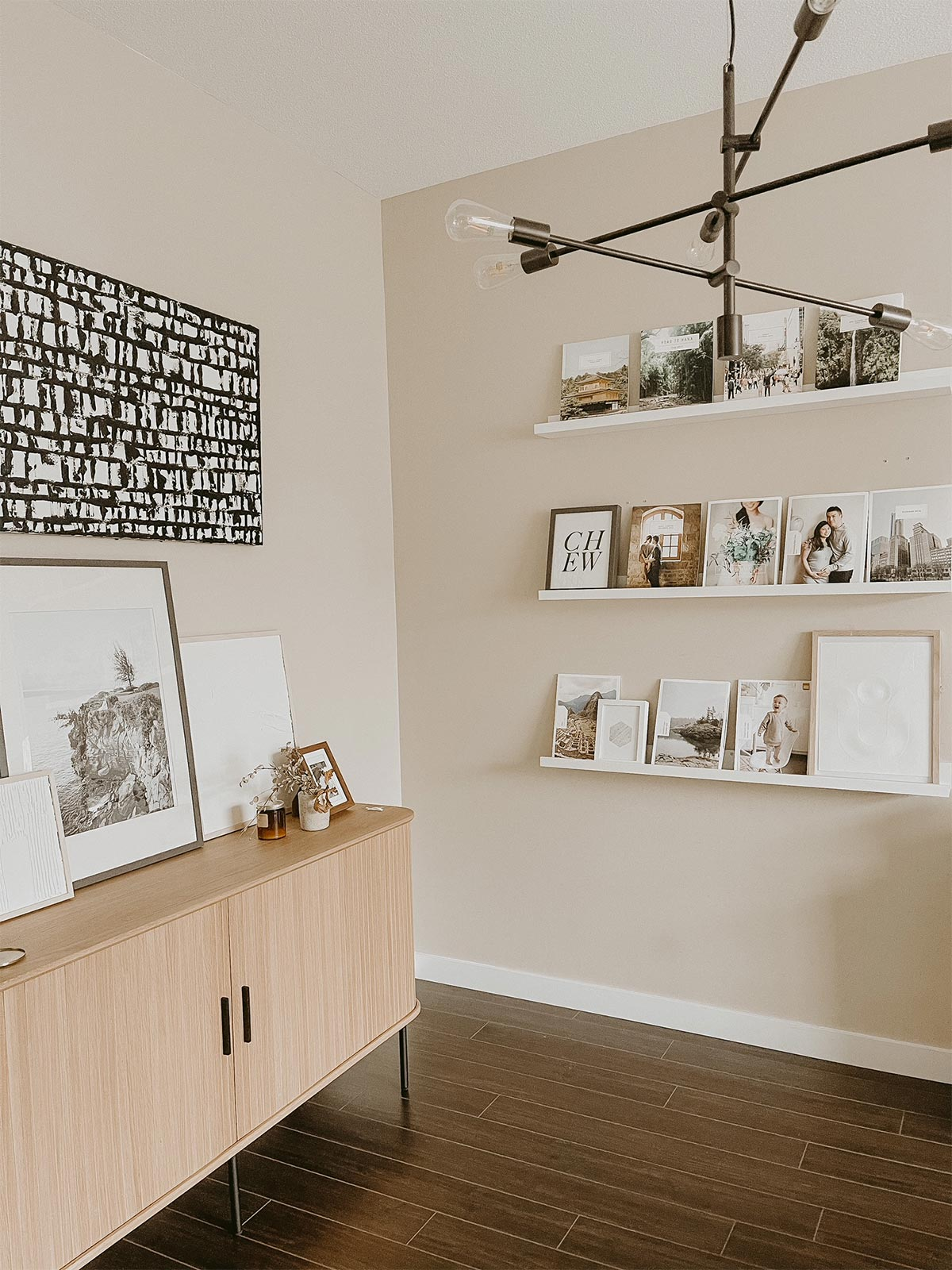 Frames, styling objects, and photo books on three floating ledges next to media console with large frame on it
