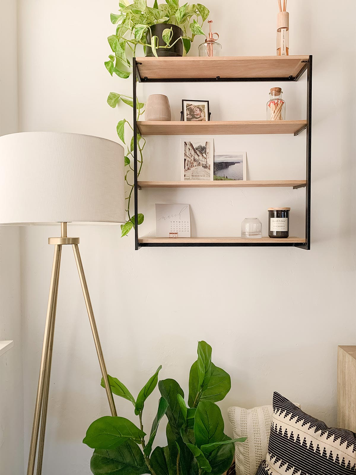 Floating bookshelf lined with Artifact uprising photo prints, decorative items, and a pothos plant