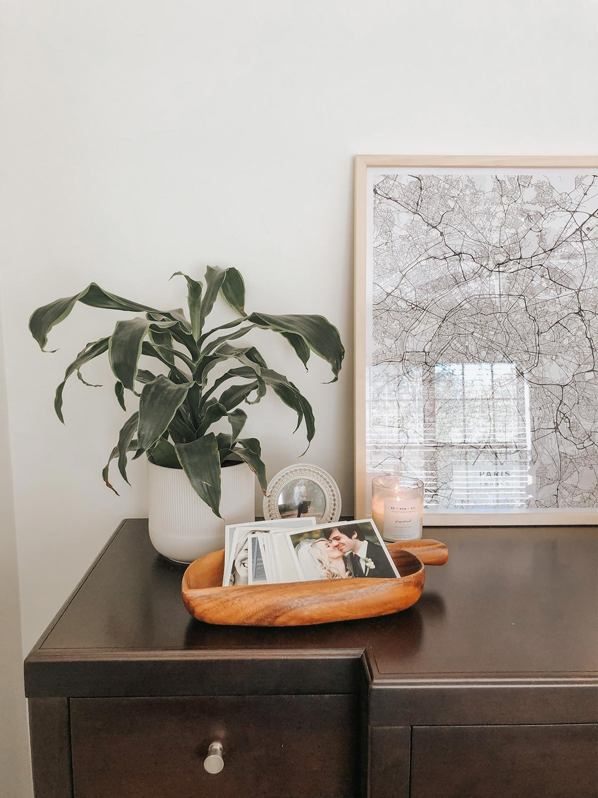 Artifact Uprising Square Prints in decorative wooden bowl on dresser next to plant and large framed photo of snow-covered tree branches