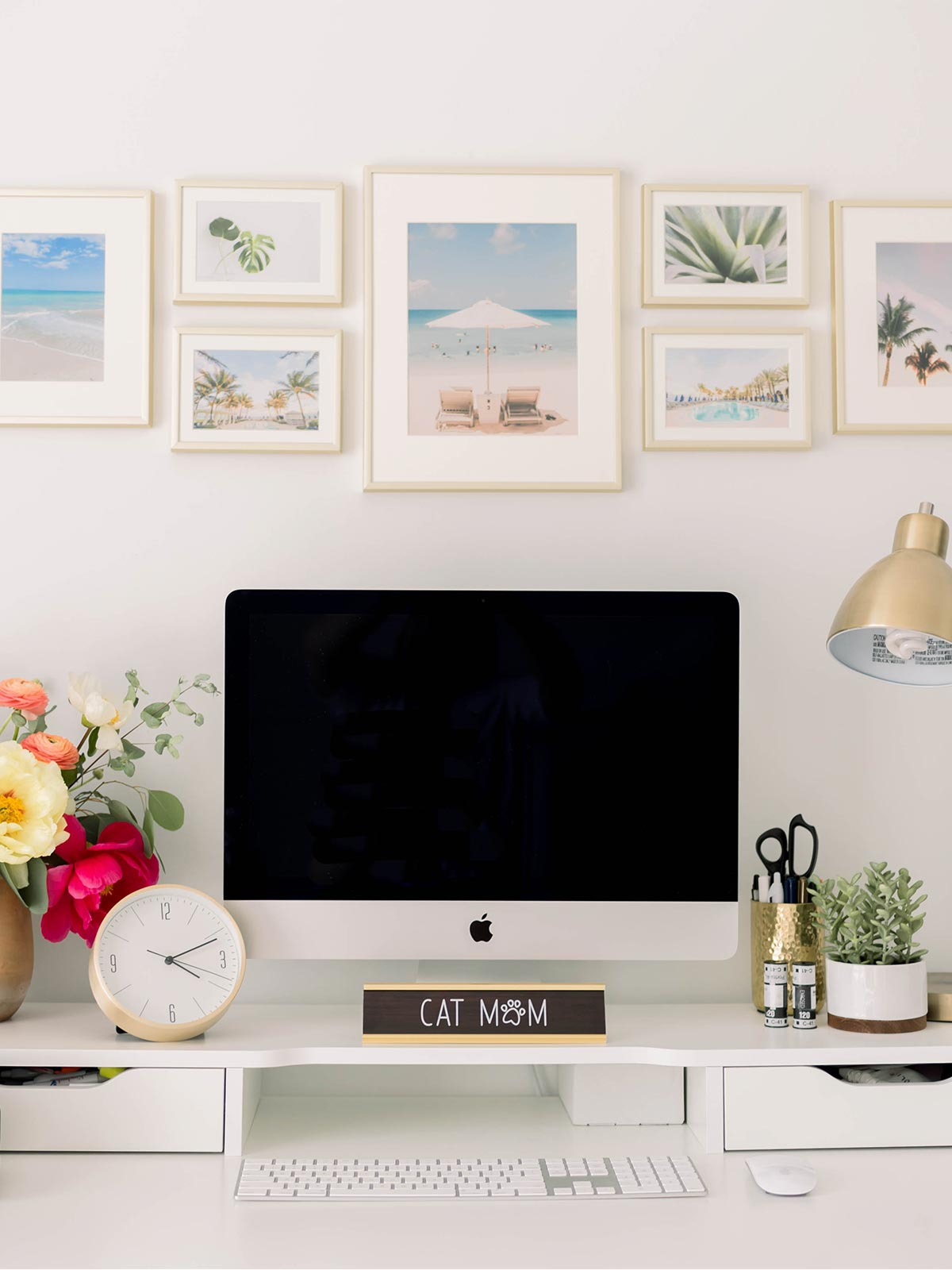 Gallery wall of frames above a desk with a computer, lamp, and bright bouquet.