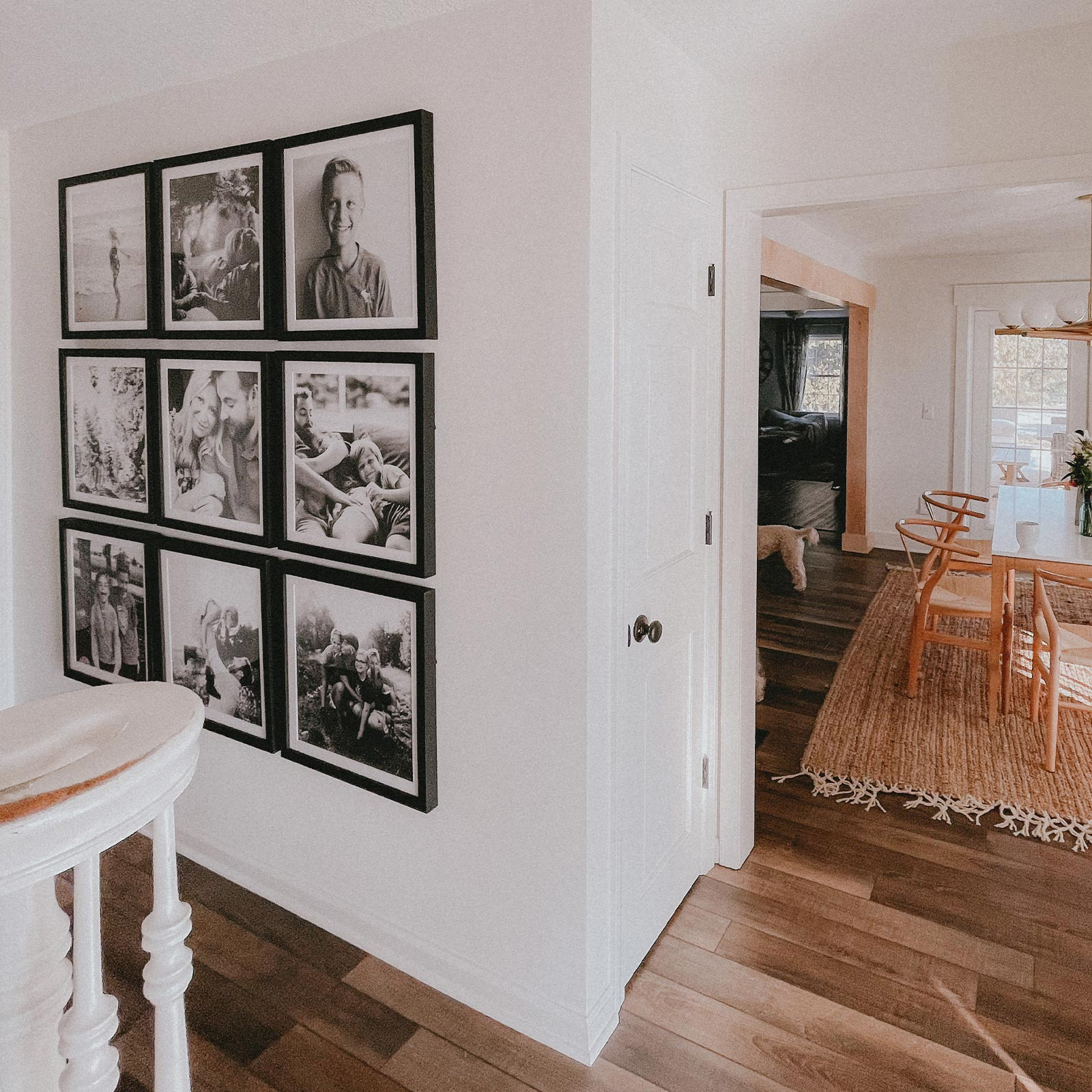 A clean, light-filled hallway with a gallery wall grid of black Artifact Uprising Gallery Frames featuring black and white family photos