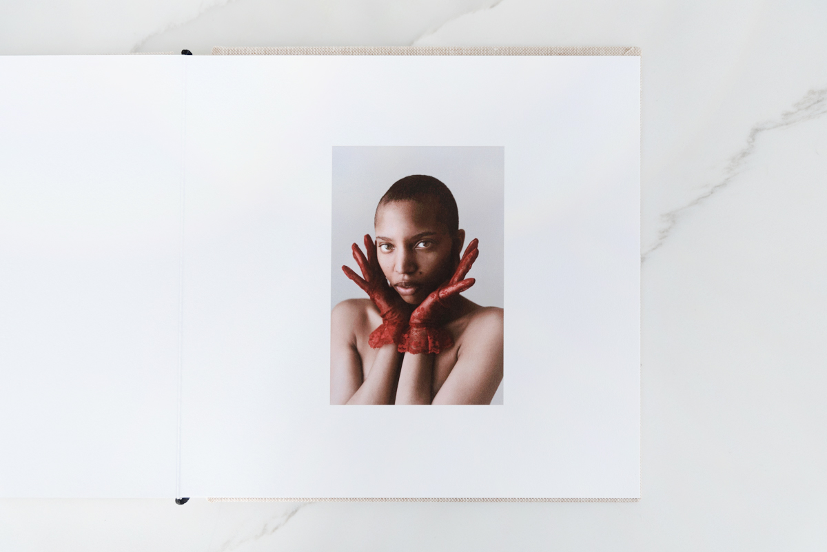Artifact Uprising Layflat Photo Album opened to portrait of woman in red gloves on right page and blank left page
