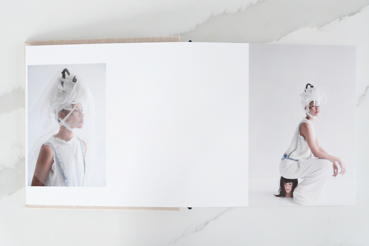 Artifact Uprising Layflat Photo Album opened to portrait of woman wearing veil on left page and same woman sitting on a manikin head on right page
