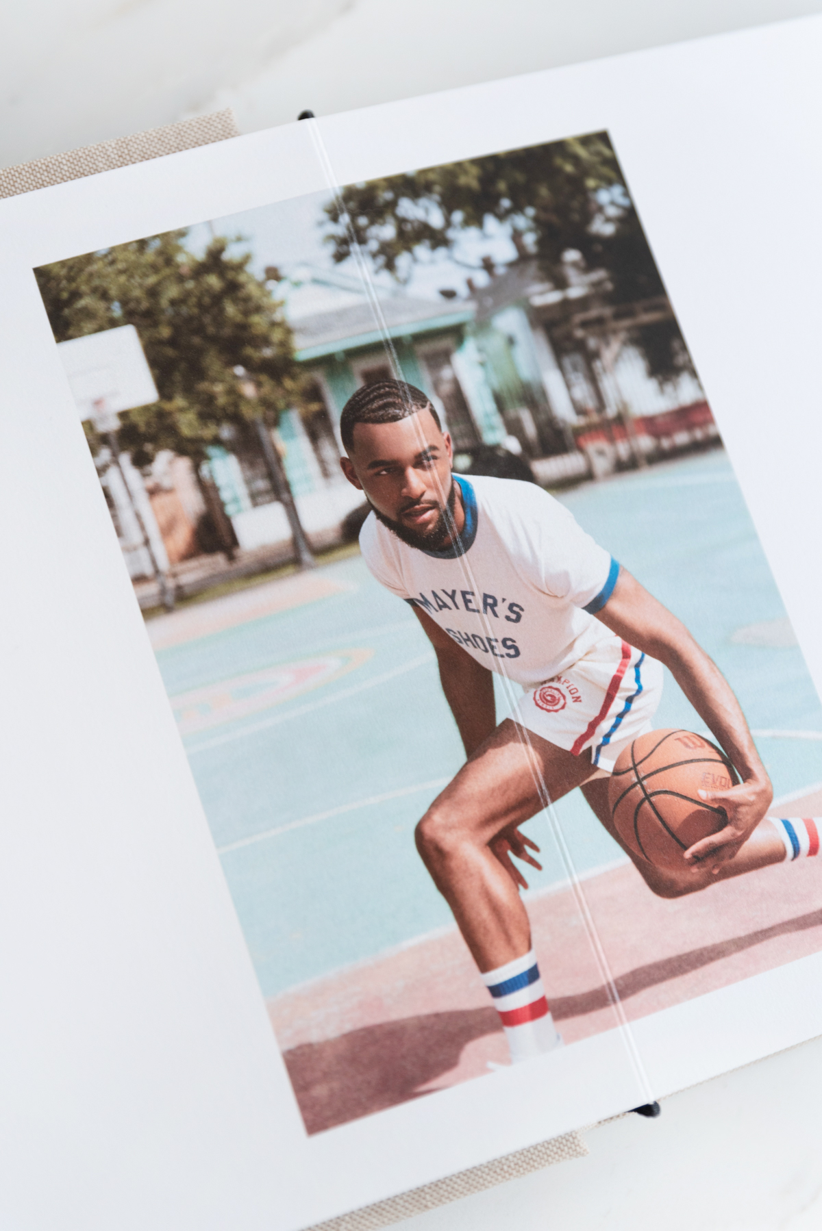 Artifact Uprising Layflat Photo Portfolio Book opened to mid-motion portrait of young man dribbling basketball between his legs