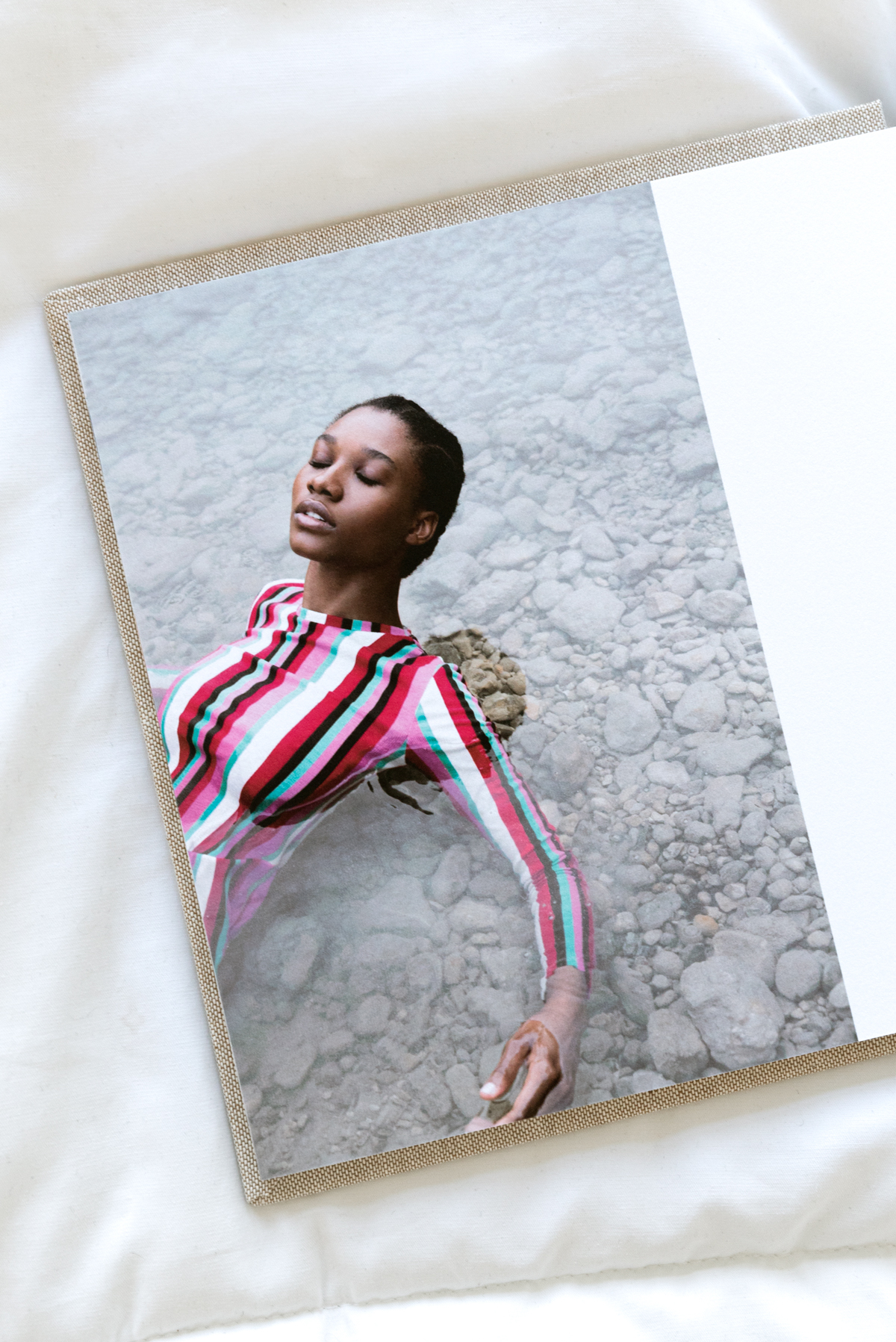 Artifact Uprising Layflat Photo Portfolio Book opened to portrait of young women in long-sleeve striped dress laying in shallow water