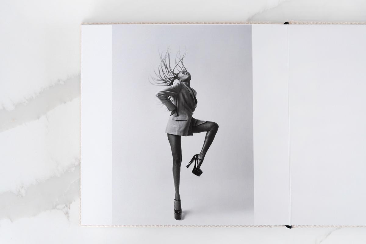Artifact Uprising Layflat Photo Portfolio Book opened to mid-motion portrait of woman in platform heels flipping hair back