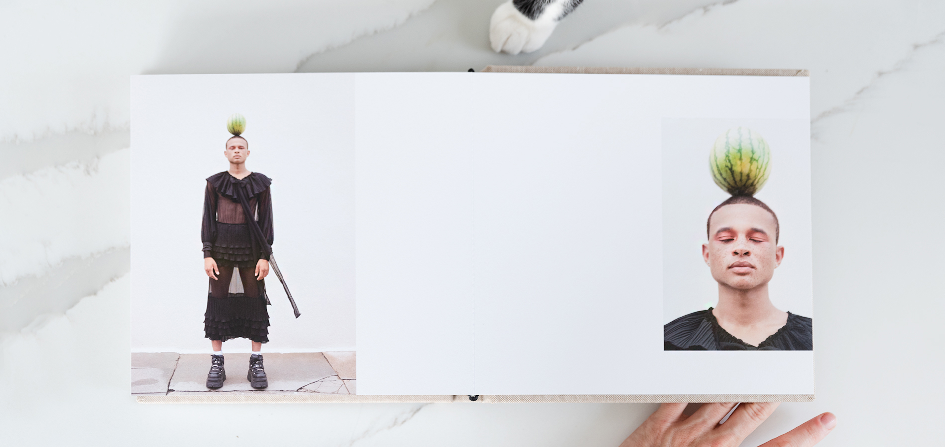 Artifact Uprising Layflat Photo Album opened to two page spread with high-fashion portrait of man balancing watermelon on his head on either page