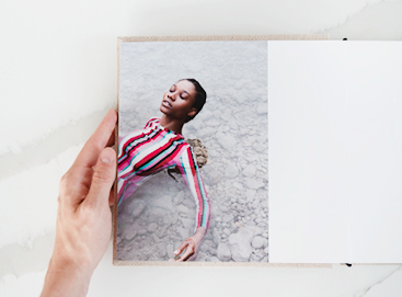 hand on edge of layflat photography portfolio book opened to image of woman in striped dress laying in shallow water