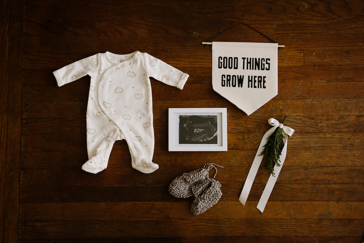 Framed sonogram laid out next to baby garments and nursery decor items
