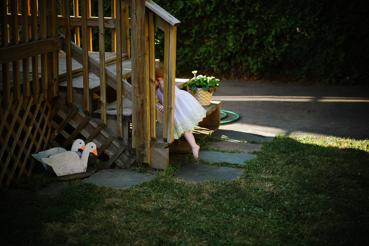 Little girl climbing up wooden patio stairs