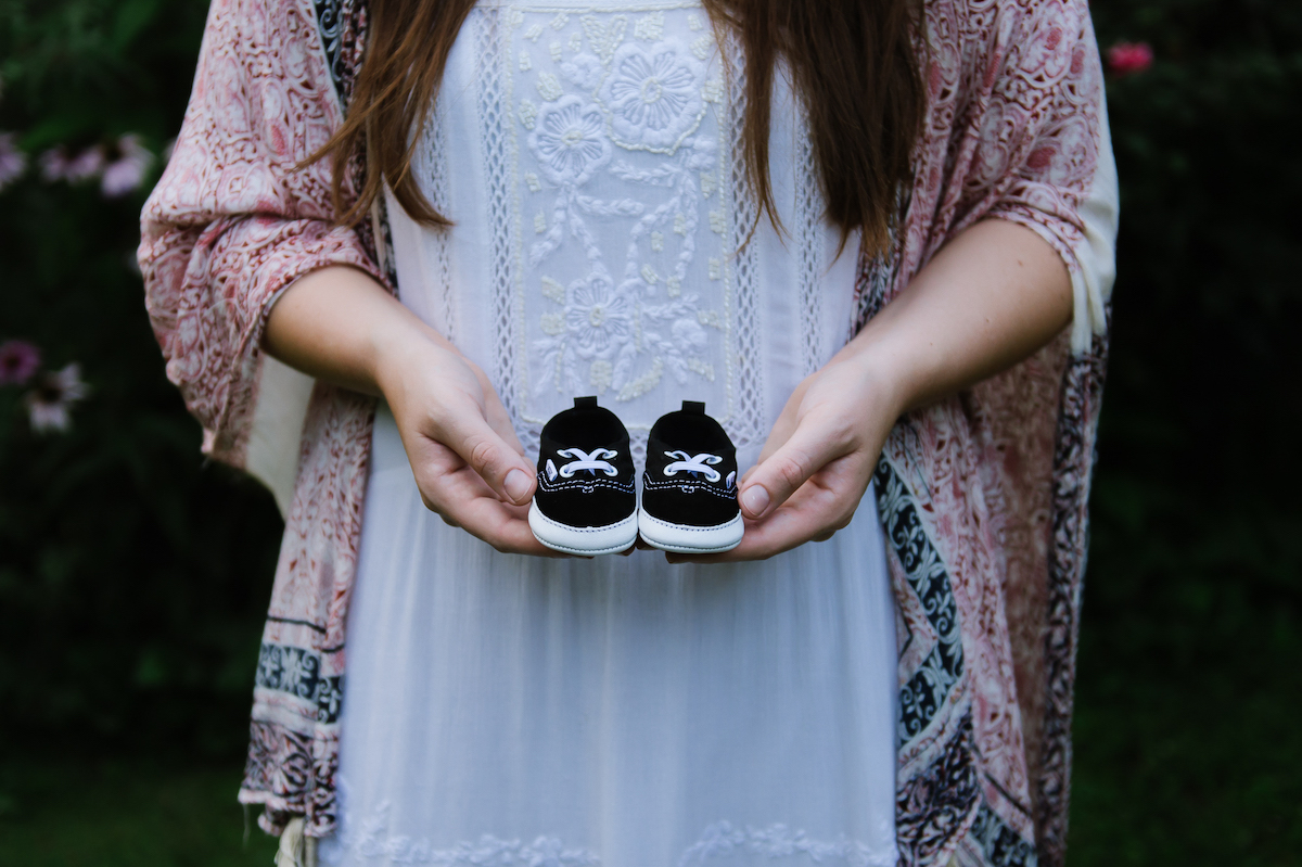 Photo by Martha Swann-Quinn of woman's hands holding up baby shoes