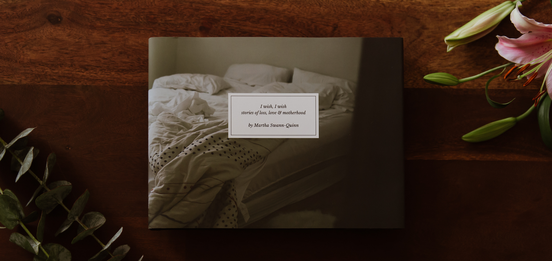 Artifact Uprising Hardcover Photo Book on wooden surface next to pink lily and eucalyptus