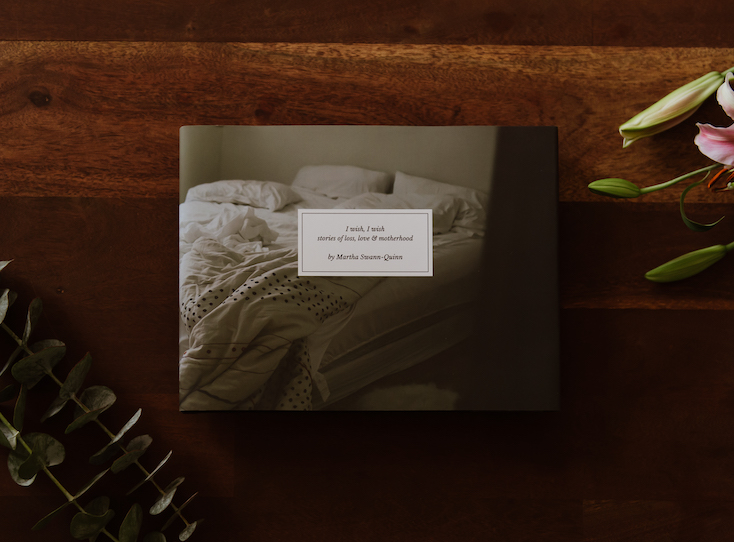 Photo by Martha Swann-Quinn of Artifact Uprising Hardcover Photo Book on wooden surface with pink lilies and eucalyptus