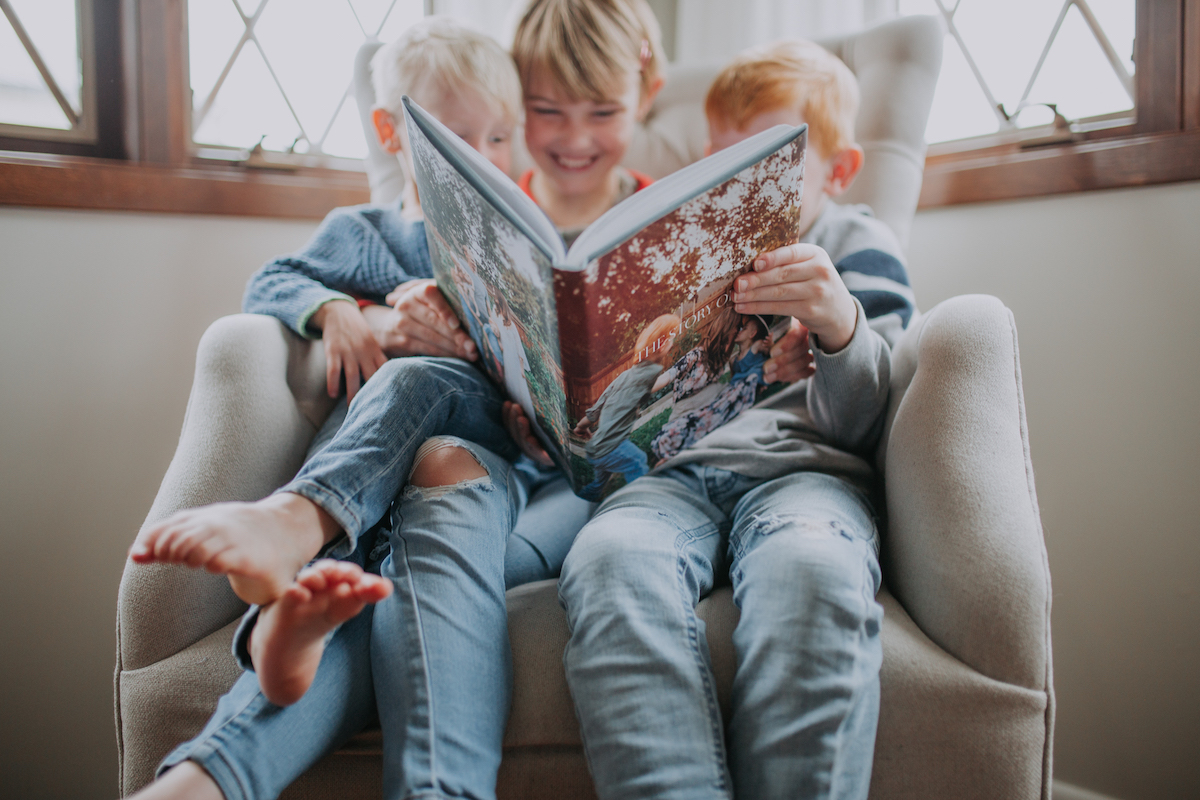 Three young children holding up Artifact Uprising Hardcover Photo Book as they flip through together on the couch