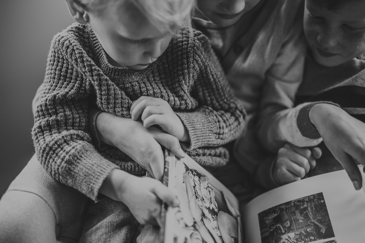 Black and white photo of three young children on same armchair flipping through Artifact Uprising Hardcover Photo Book