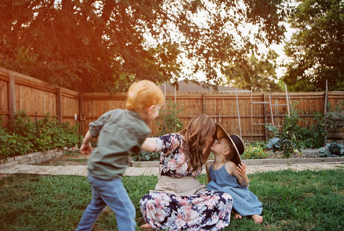 Mother kissing her little girl as she swings her little boy around with one arm