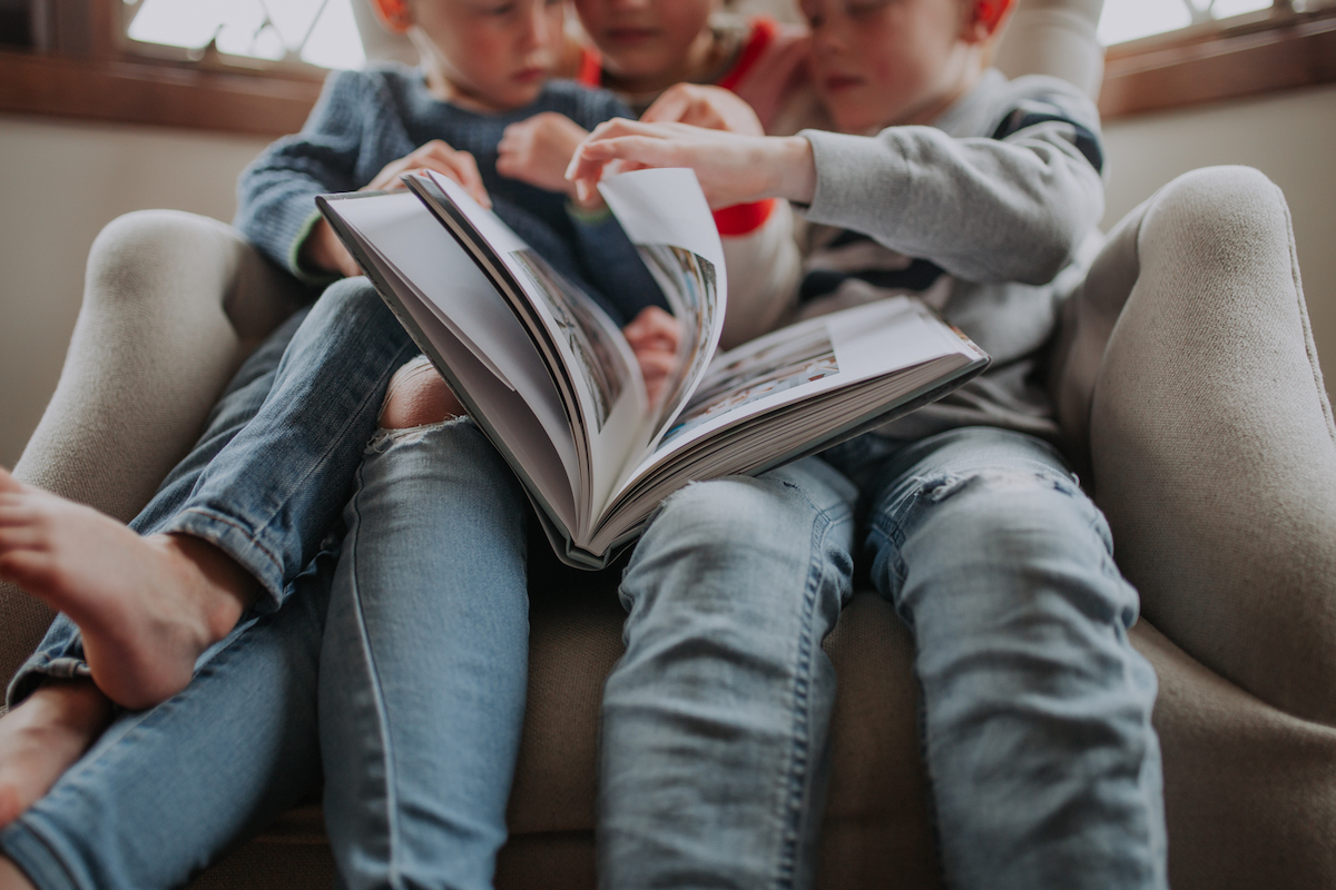 Three young children on couch looking through Artifact Uprising Hardcover Photo Book as they all try to turn the page at once