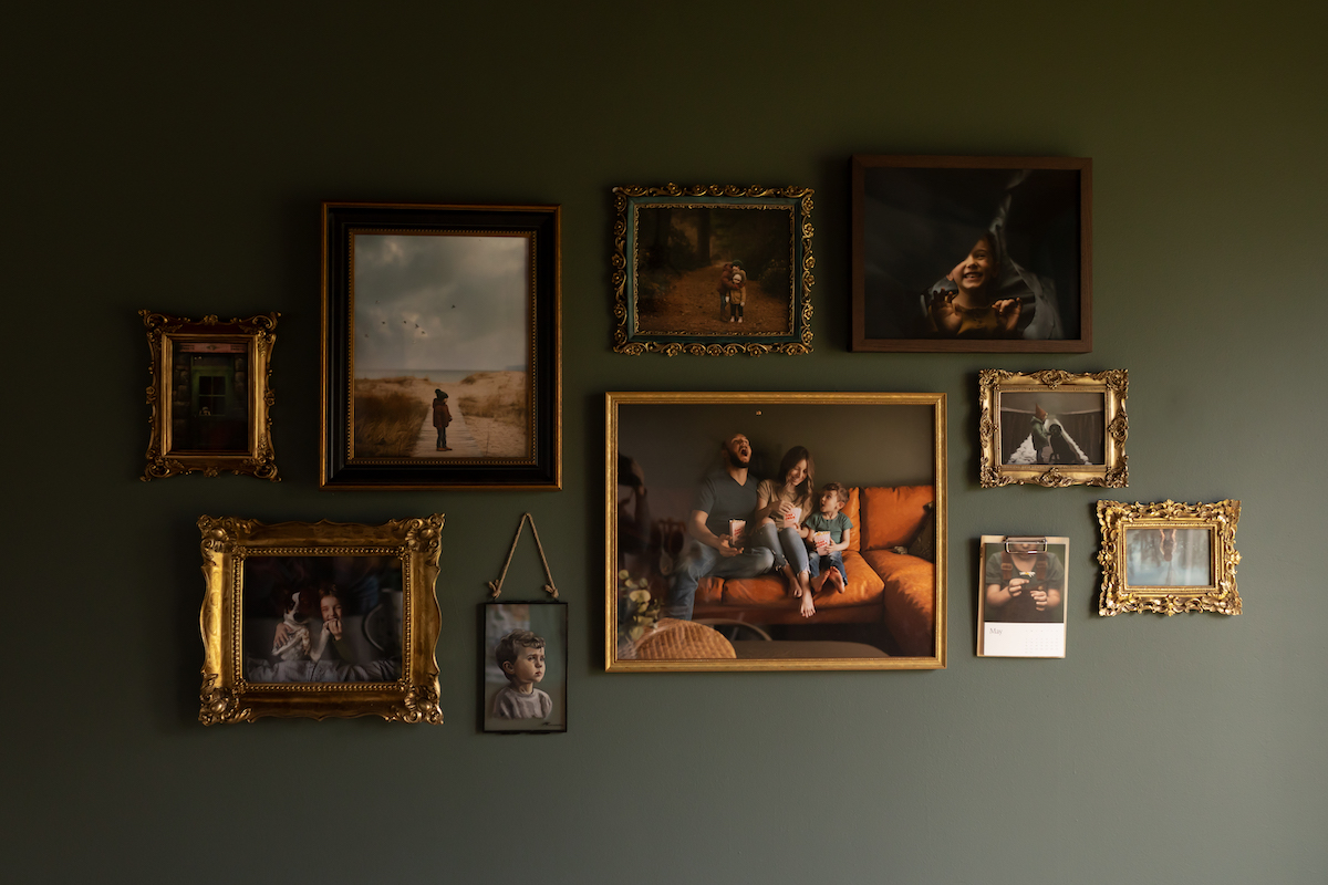 Gallery wall featuring family photos in gold and brass frames hung on dark olive green wall