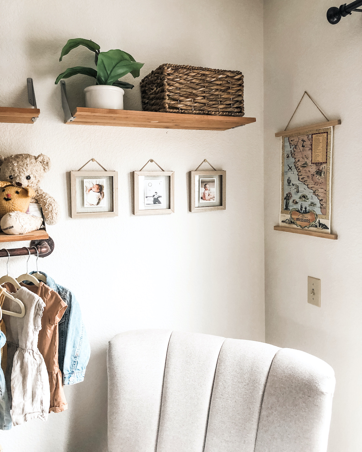 Trio of framed Artifact Uprising Everyday Photo Prints on nursery wall below floating shelf and above armchair
