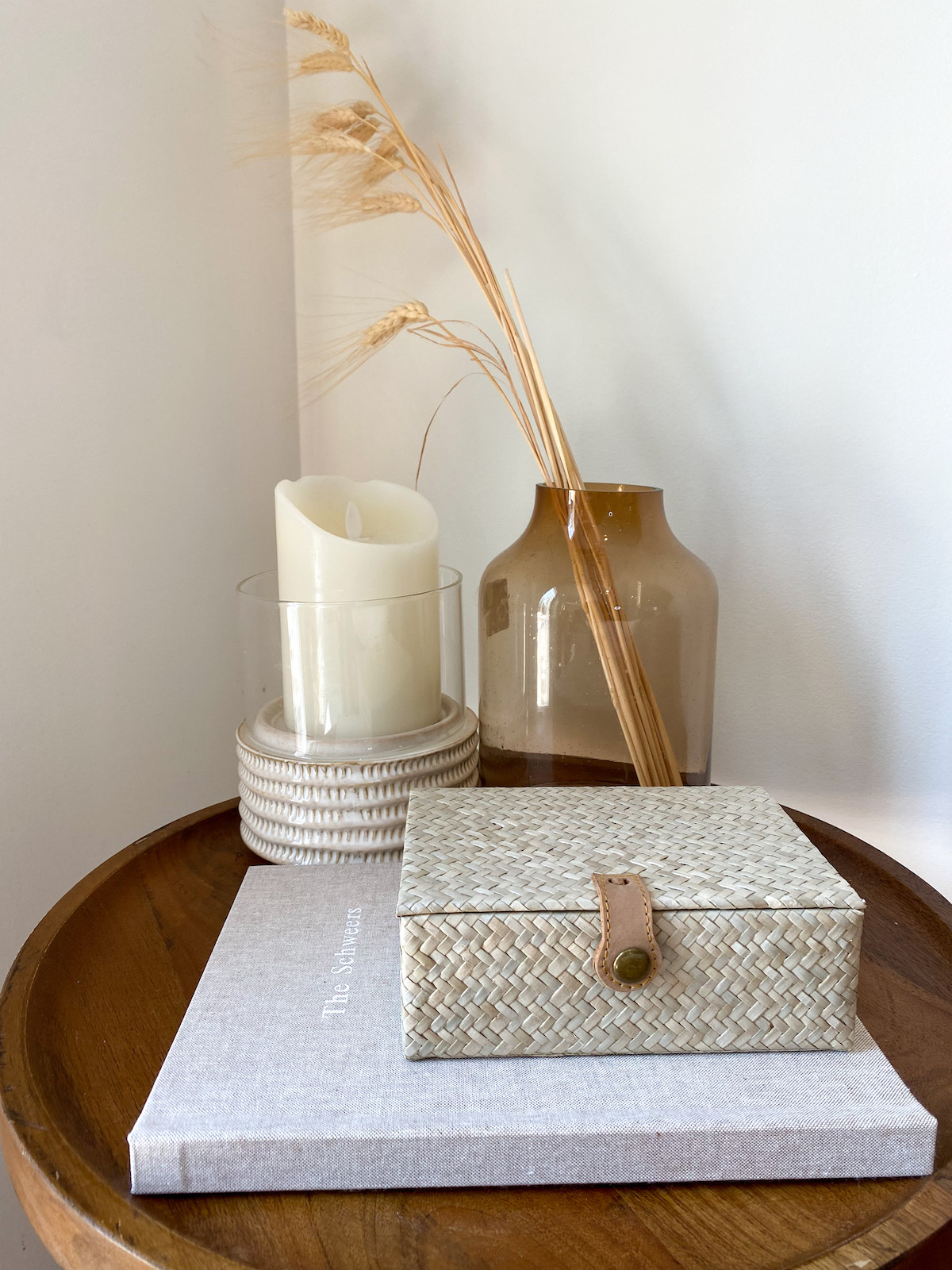 Circular side table with candle, dried straw in glass vase, and Artifact Uprising Layflat Photo Album