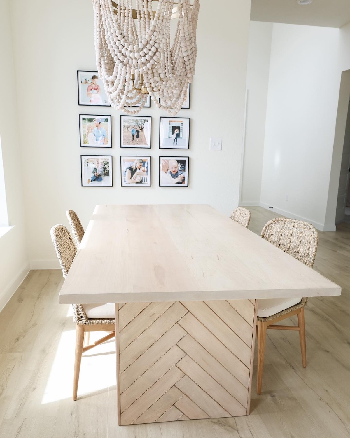 9 frame grid gallery wall in minimalist dining room featuring family portraits in Artifact Uprising Modern Metal Frames behind dining table and roped chandelier