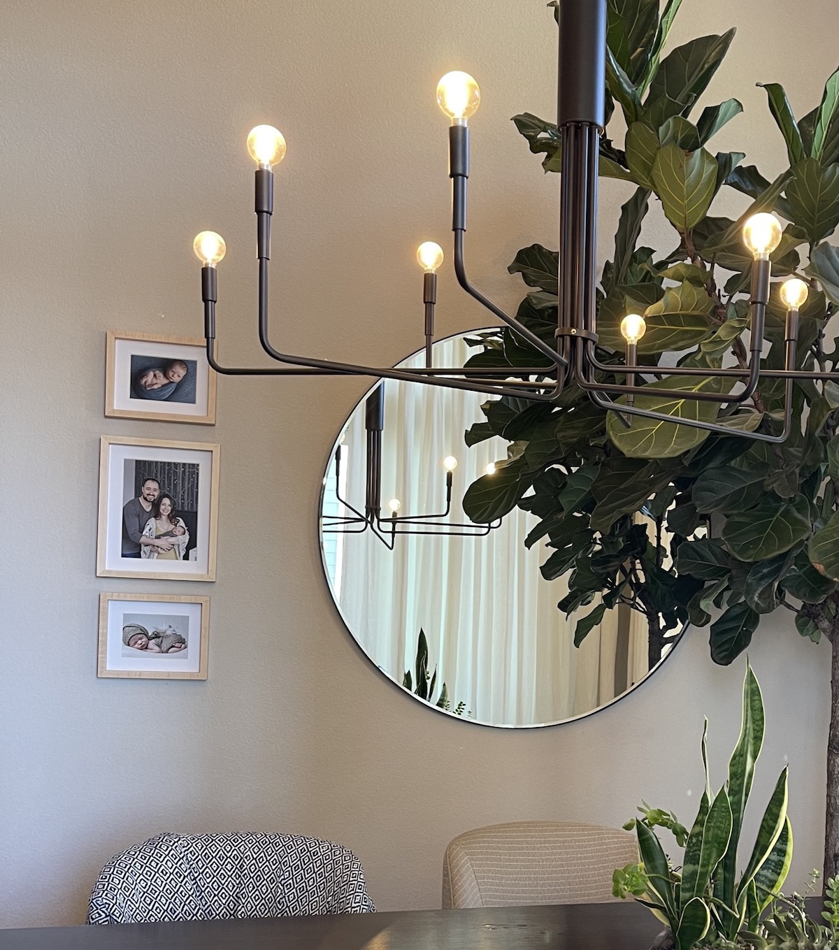 An Artifact Uprising Wooden Tabletop Frames hung in vertical trio on dining room wall next to circular mirror behind a modern chandelier