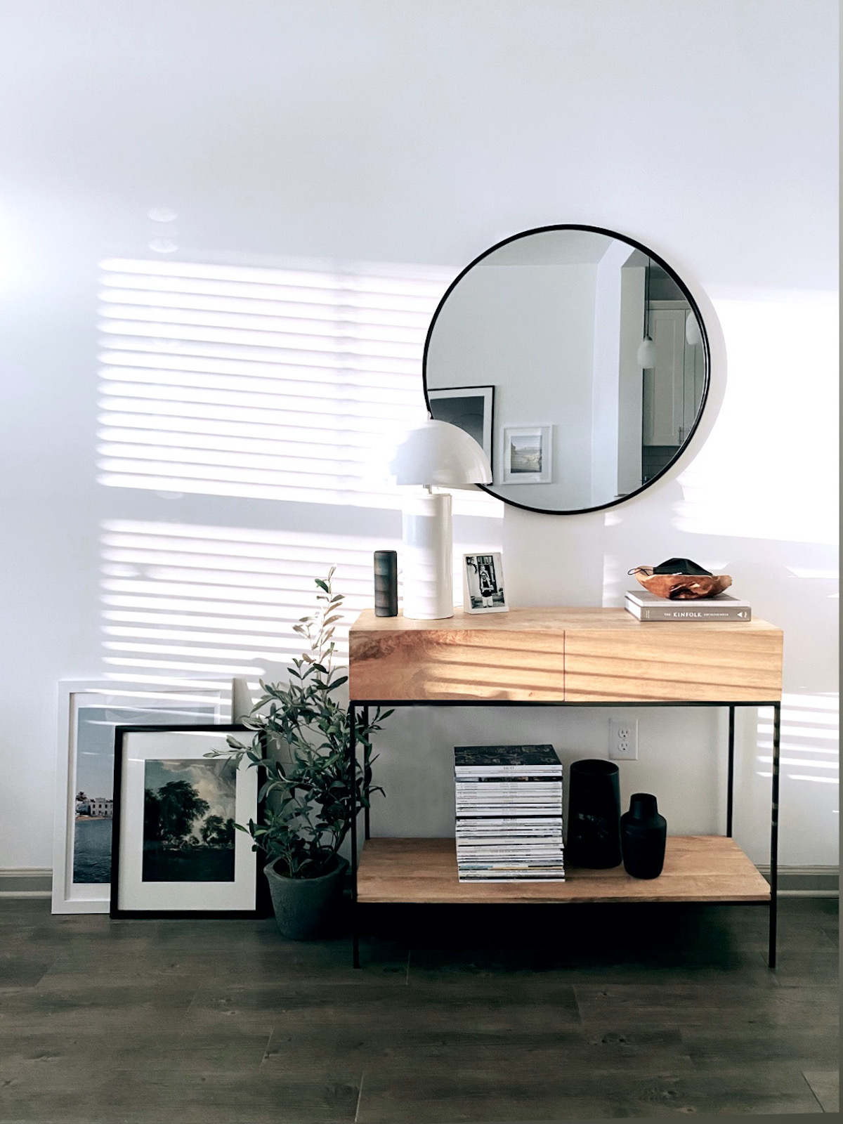Two large Artifact Uprising Gallery Frames on the ground layered one in front of the other against the wall next to a credenza, house plant, and mirror