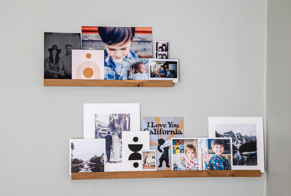 Two Artifact Uprising Wooden Photo Ledges filled with Everyday Prints and other family photos and art prints