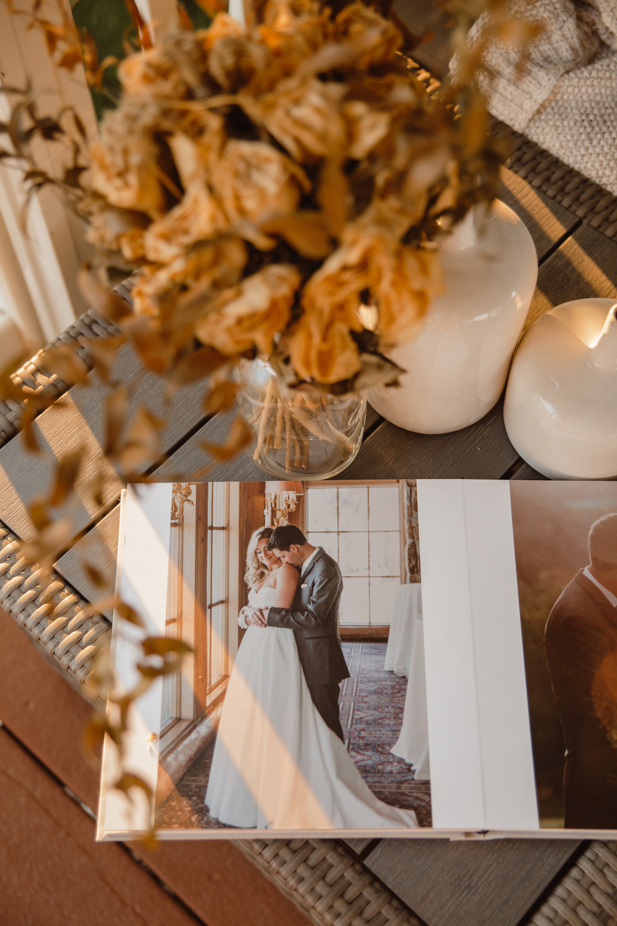 Overhead photo of dried botanicals in glass vase on side table next to Artifact Uprising Wedding Layflat Photo Album