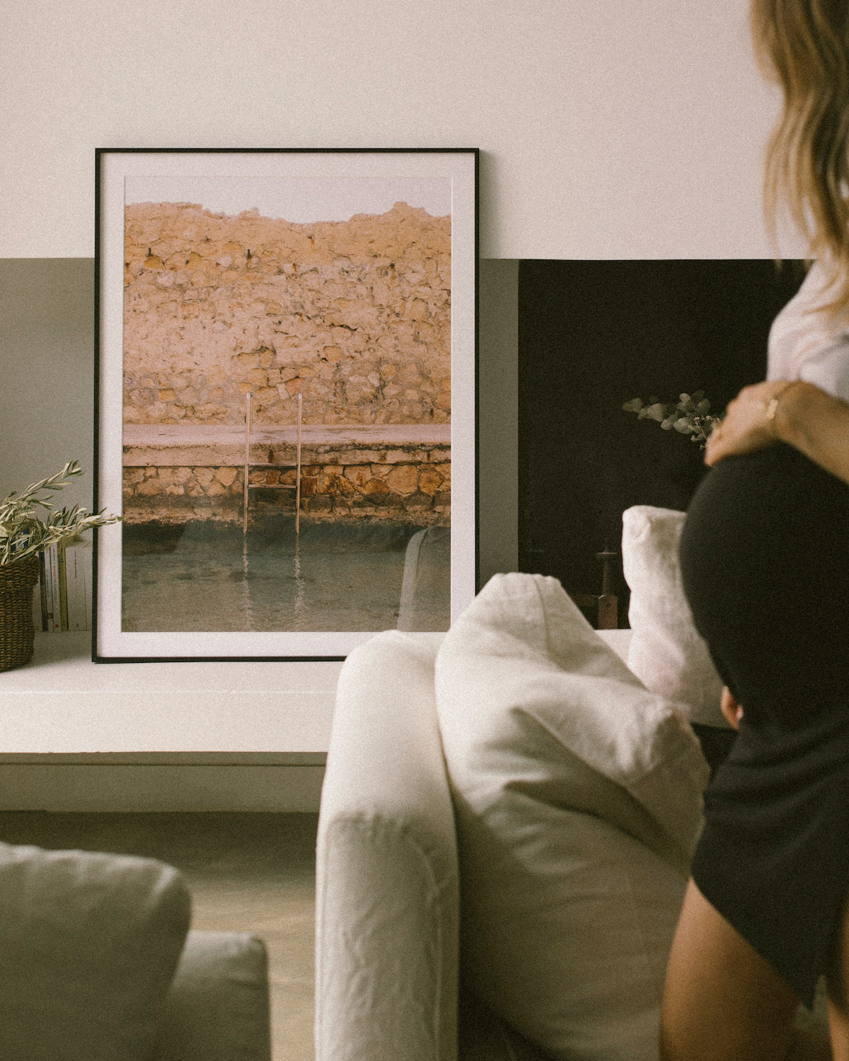 Pregant woman holding belly as she looks at large Artifact Uprising Modern Metal Frame placed on mantel next to fireplace