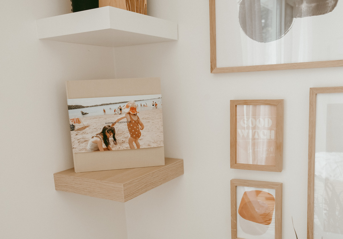 Artifact Uprising Hardcover Photo Book featuring photo of tow little girls at the beach placed on small corner wall shelf next to gallery wall of frames